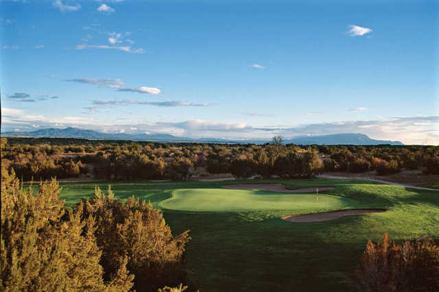 A view of a green protected by tricky bunkers at Cochiti Golf Club