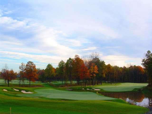 A fall view of a green flanked by sand traps and a pond at Thundering Waters Golf Club