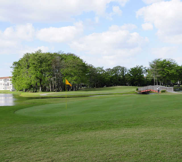 A view of a green with a bridge in background at Colony West Country Club