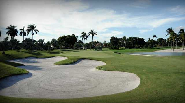 A view of a green protected by undulating bunkers and a pond at La Gorce Country Club