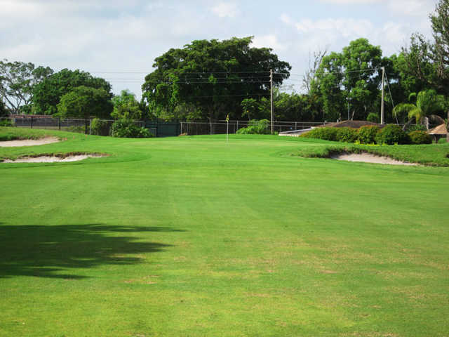 A view of a green guarded by sand traps at Ocean Breeze Golf & Country Club