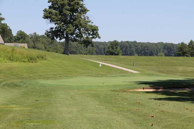 A view of a green with a narrow path in background at Hidden Hills Golf Course