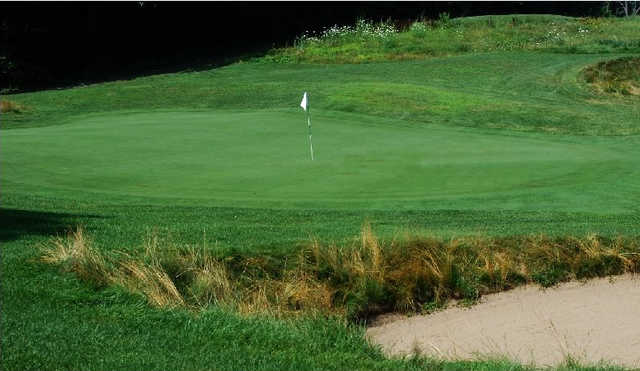 A view of a hole protected by a bunker at Calderone Golf Club