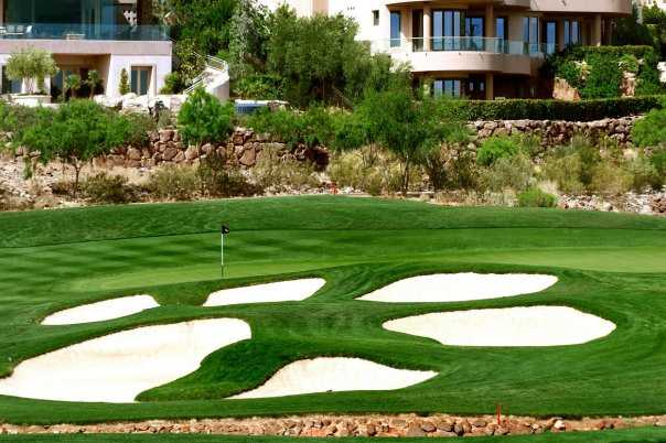 A view of a green surrounded by a collection of bunkers at DragonRidge Golf Course