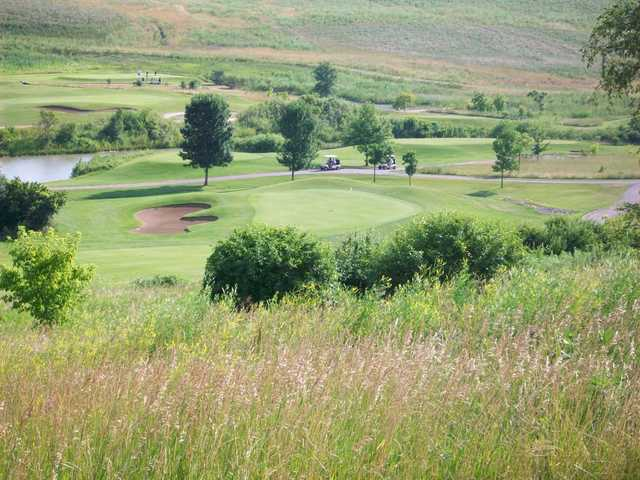 A view of a green protected by a bunker at Settler's Hill Golf Course