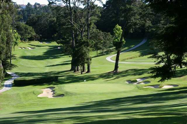 A view of a hole surrounded by sand traps at Green Hills Country Club