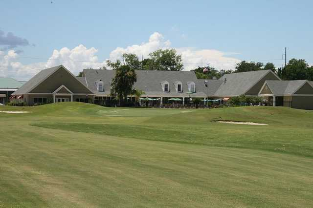 A view of a green and the clubhouse at Cypress Lakes Country Club.