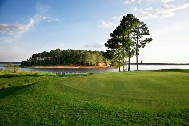 A view of a green with water in background at Cypress Bend Golf Resort