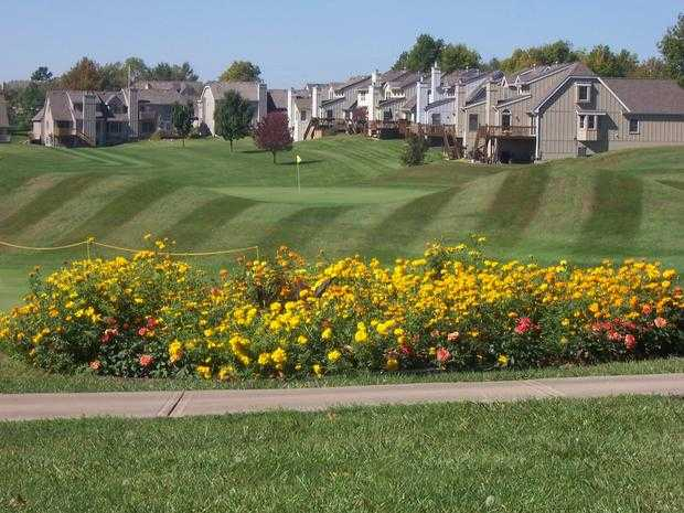 A view of a green surrounded by flowers at Teetering Rocks Links