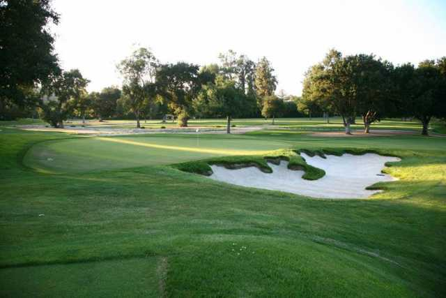 A view of a green protected by a bunker at Woodland Hills Country Club