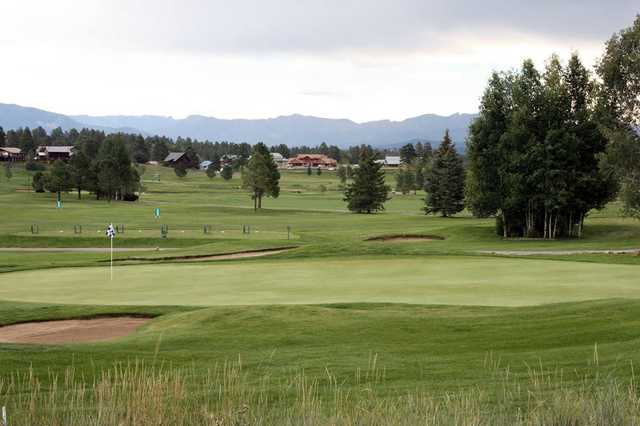 A view of a green protected by bunkers with the driving range in background at Pagosa Springs Golf Club