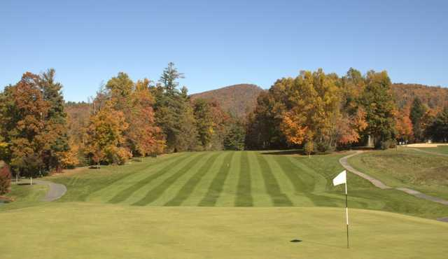 A view of a green with a narrow path on the left side at Boone Golf Club