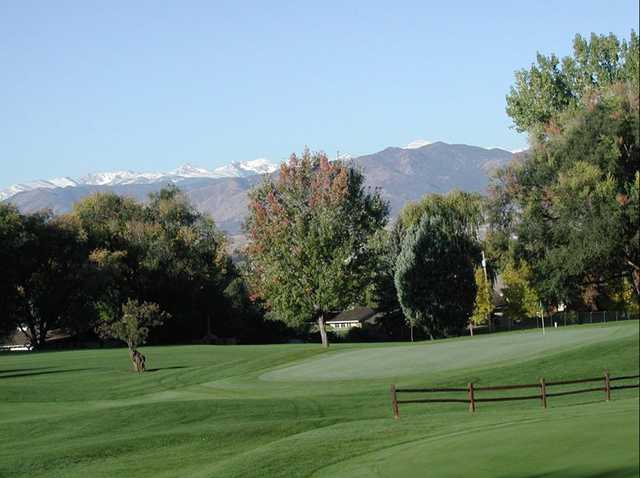 A view of a green with mountains in background at Sunset Golf Course