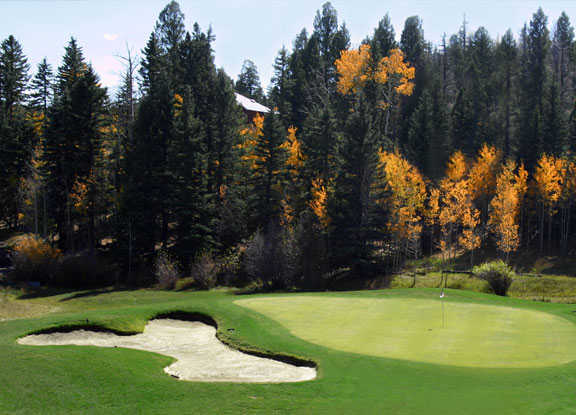 A fall view of a green protected by a large bunker at Angel Fire Resort Country Club