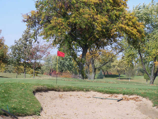 A view of a green guarded by a sand trap at Bloomingdale Golf Course