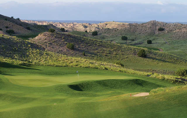 A view of a green with water in the distance at Black Mesa Golf Club