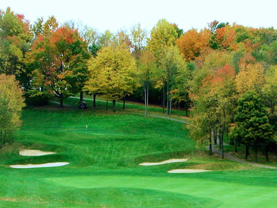 A view of a green protected by a collection of bunkers at Deer Ridge Golf Club