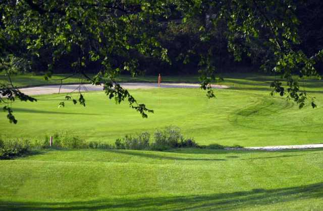 A view of a green guarded by an undulating bunker at Orangeville Golf Club