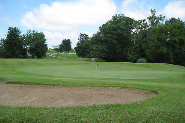 A view of a green protected by a bunker at Hickory Ridge Golf Center