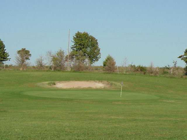 A view of a green protected by a bunker at Eagle Crest Golf & Country Club