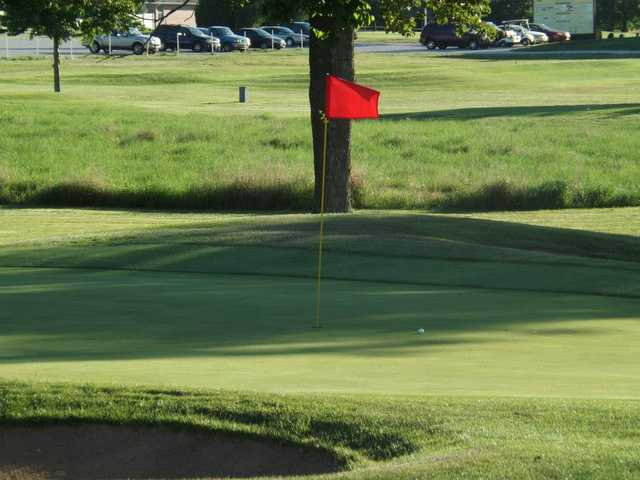 A view of a green protected by a bunker at Whispering Oaks Golf Course