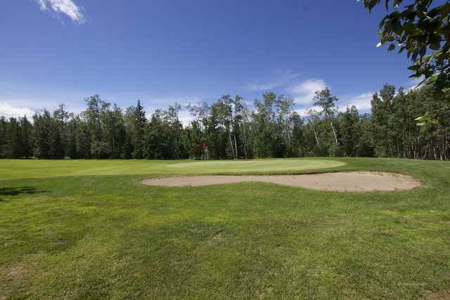A view of a green protected by a bunker at Pipestone Golf Club