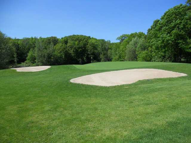 A view of a green protected by sand traps at Woodhaven Country Club
