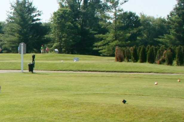 A sunny day view of a tee at Pine Lakes Golf Course