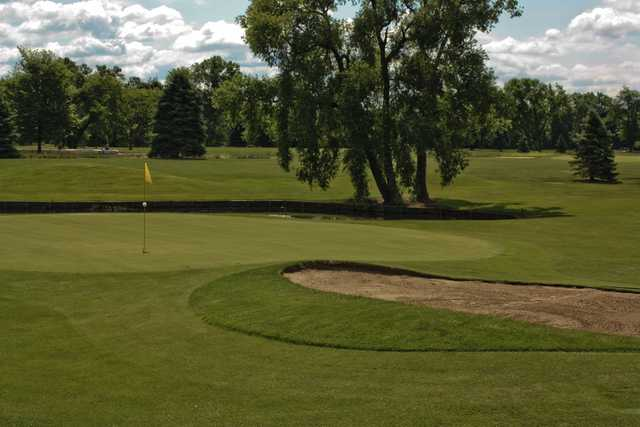 A view of a green protected by a pond and a bunker at Gold from Winding Creek Golf Course