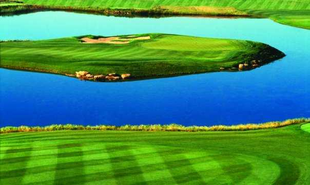 A view of a green surrounded by water at Shadow Lakes Golf Club