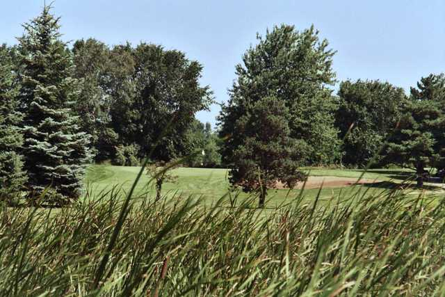 A view of a hole protected by a bunker at Maple Creek Golf Club