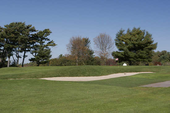 A view of a green protected by a bunker at North Hill Country Club