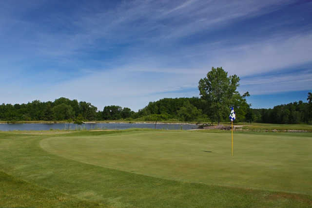 A view of a green with water in background at Idlewild Golf Course
