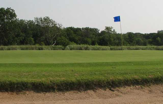 A view of a green protected by a sand trap at Falconhead Resort & Country Club