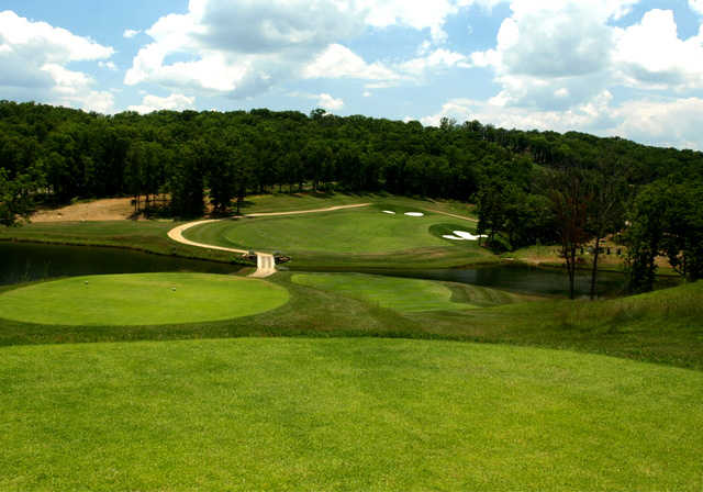 The par-4 17th at Branson Hills Golf Club plays from an elevated tee over a lake.