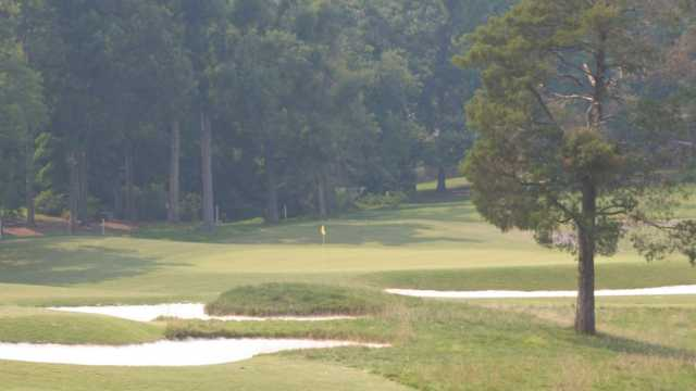 A view of a green protected by sand traps at Forest Oaks Country Club