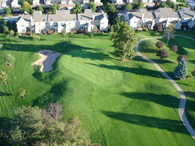 A view of a green with a narrow path on the right side at PineCrest Country Club