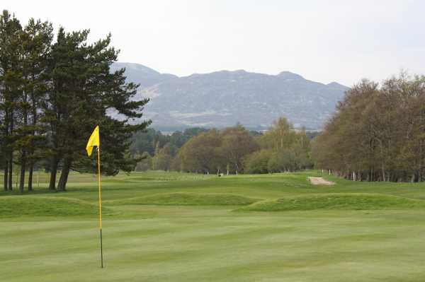 A view of a hole with mountains in background at Newtonmore Golf Club