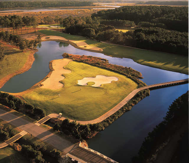 Aerial view of the 12th green surrounded by the water.