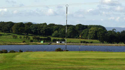 A view of a green with water in background at Fereneze Golf Club