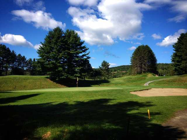 A view of a green protected by a bunker at St. Johnsbury Country Club