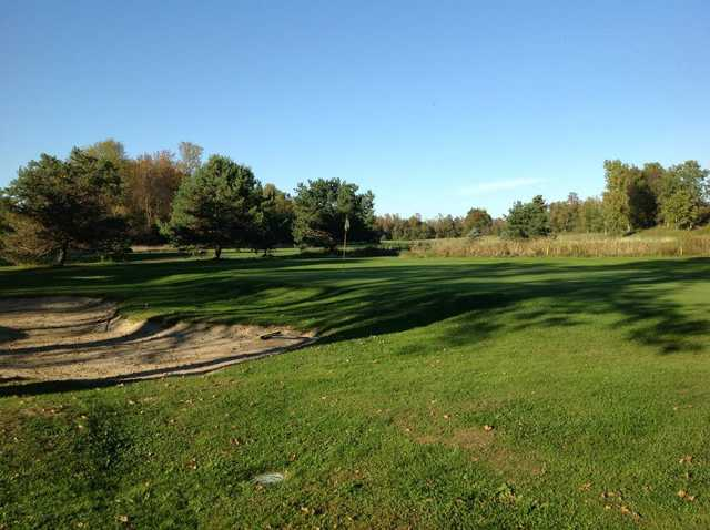 A view of a green protected by a bunker at Alburg Country Club