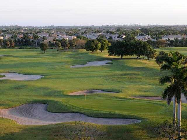 A view of a green protected by a collection of bunkers at Heron Bay Golf Course