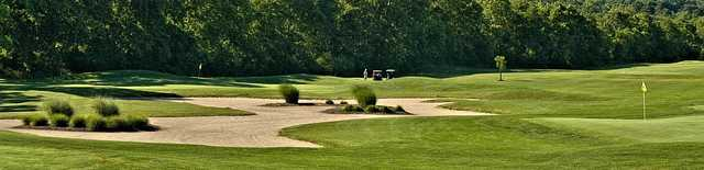 A view of a green protected by a bunker at Robin's Nest Golf Course