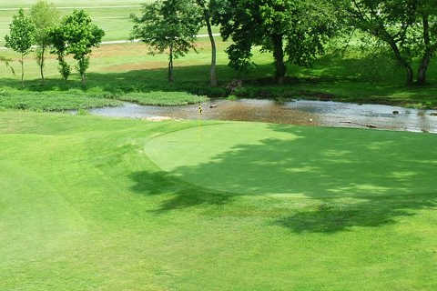 A view of a green with water coming into play at the Creeks Golf & RV Resort