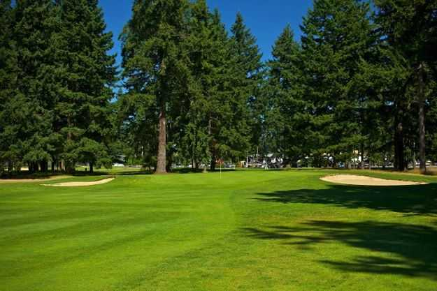 A view of the 16th green flanked by bunkers at Lake Spanaway Golf Course