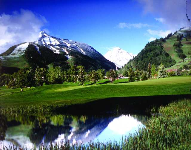 A view of a green with snowy mountains in background at Aspen Golf Course