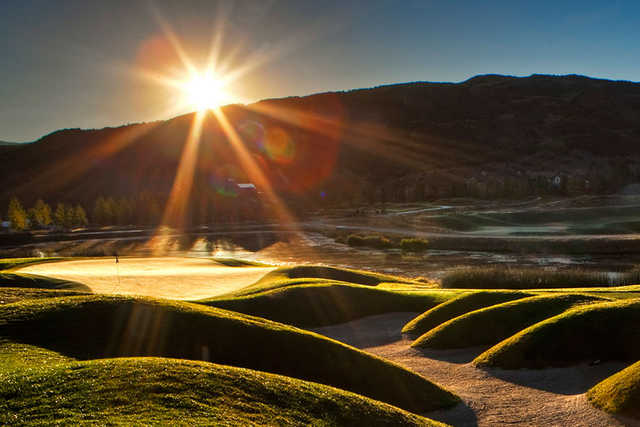 A sunny view of a green at Snowmass Club Golf Course