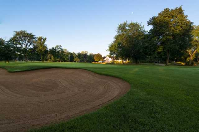 A view of a hole protected by a large bunker at Deerpath Golf Course