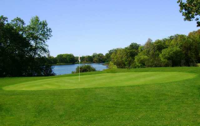 A view of a green with water in background at Hardwood Hills Golf Course